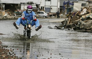 24 hours in pictures: A man rides a motorcycle through Ishinomaki, Japan