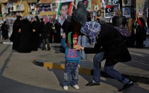 24 hours in pictures: a young girl  flashes a victory sign in Benghazi, Libya