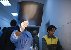 24 hours in pictures:  A doctor inspects the X-ray of a wounded Libyan rebel fighter