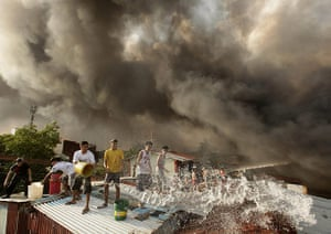 24 Hours in Pictures: Filipinos try to control a blaze as smoke rises from burning shanties