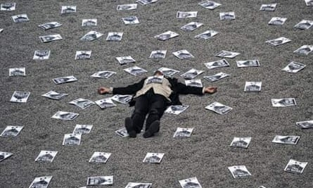 A demonstrator surrounded by posters lies in Ai Weiwei's sunflower seeds exhibit in the Tate Modern.