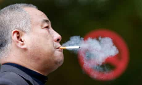 """A man smokes next to a """"No Smoking"""" sign in downtown Shanghai"""