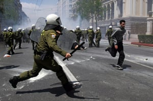 Protests in Athens: A police officer runs in riot gear after clashes erupted during a strike