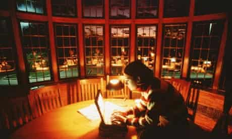 Young woman using laptop by lamp light