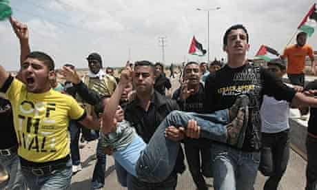 Palestinians carry a boy hurt after Israeli troops fired on people marching on Gaza-Israeli border