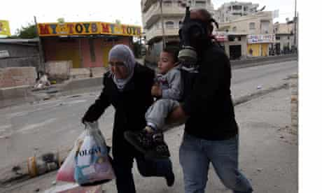 Palestinian man in gas mask helps woman and child during Nakba Day clashes