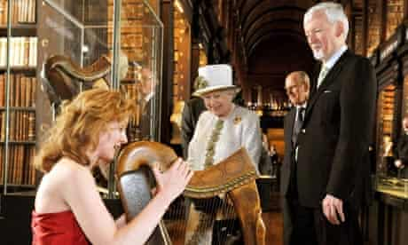 Queen Elizabeth Il listens to harpist Siobhan Armstrong as she visits Trinity College Dublin