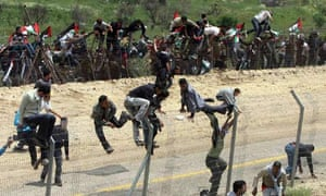 Protesters climb the fence between Syria and Israel