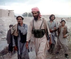 Osama bin Laden: 1989: Osama Bin Laden walks with Afghanis in the Jalalabad area