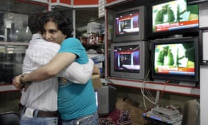 Afghan men hug each other while watching news of the death of Osama bin Laden