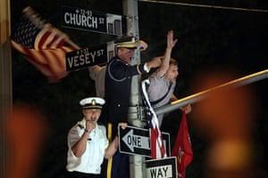 Bin Laden US reaction: Servicemen hang off a lamp post cheering in celebration at Ground Zero