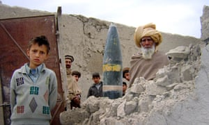 Pakistani tribesmen stand by a fired mis