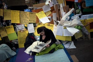 Spain protests: a demonstrator reads a newspaper