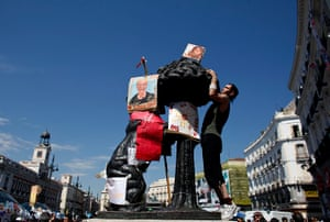 Spain protests continue: A demonstrator puts up banners on the square's main statue of a bear