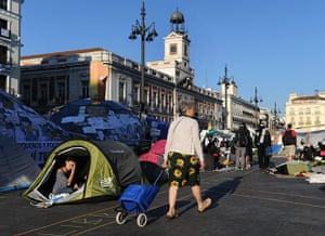 Spain protests continue: A woman passes tents and banners of protestors continuing to camp out