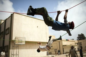 24 hours: Misrata, Libya: Young men hold ropes during a military training exercise