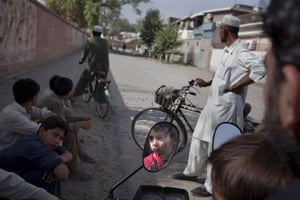 24 hours: Peshawar, Pakistan: A boy is reflected in a side mirror of a motorcycle