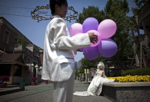 24 hours: Tianjin, China: A groom holds balloons as his bride poses for photographs