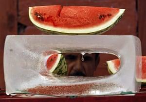 24 hours: Srinagar, India: A Kashmiri vendor sells watermelons on a melting ice block