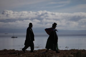 24 hours: Desaguadero, Bolivia: People walk on the shore of the Titicaca Lake