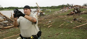 Tornadoes in US: A Sheriff Deputy akes a photo of the debris path of a tornado