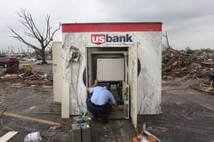 Tornadoes in US: An armoured car courier works on salvaging cash from an ATM