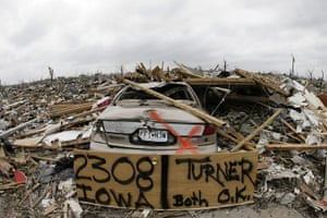 Tornadoes in US: A door with a home owner's address, rests against a destroyed car in Joplin