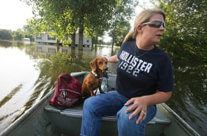 FTA Mario Tama: A woman rides with her dog Bo near her home on the Mississippi River