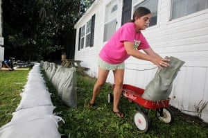 FTA Mario Tama: A woman moves sandbags with a toy wagon as she constructs a sandbag berm