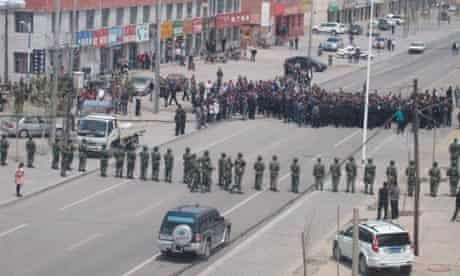 Policemen block the street during a protest in Xilinhot, Mongolia