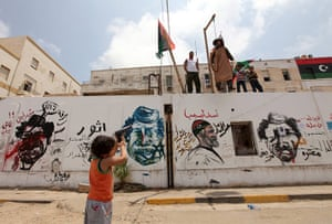Middle East Unrest: A boy points a toy gun to the effigy of Muammar Gaddafi in Benghazi