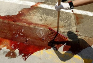 Middle East Unrest: A worker washes away blood at Misrata's hospital