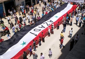 Middle East Unrest: Syrian Kurds hold a huge Syrian flag