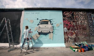 German artist Birgit Kinder paints her picture Trabi at the East Side Gallery in Berlin, Germany