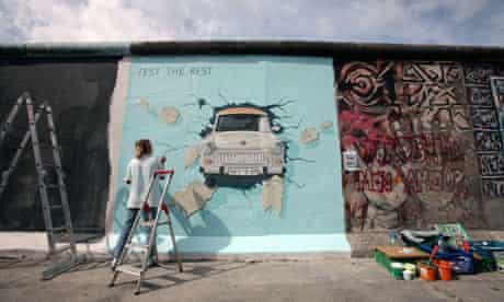 German artist Birgit Kinder paints her picture Trabi at the East Side Gallery in Berlin, Germany