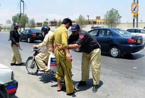 Pakistan : A policeman searches a man on a road linked to the US consulate in Karachi