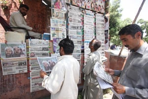 Pakistan : Men read newspapers on the death of Osama Bin Laden, in Islamabad