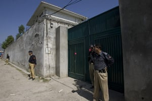 Pakistan : Police officers secure the perimeter, with a sealed gate into the compound