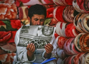 Pakistan : A man selling carpets reads a local newspaper in Quetta