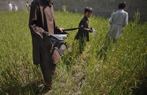 Pakistan : Boys collects debris, remains of a firefight, outside the compound