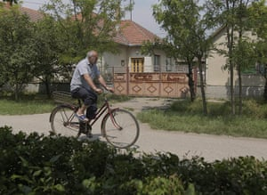 Ratko Mladic: 28 May 2011: A man rides a bicycle past the house where Mladic was found