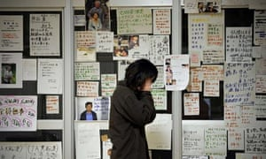 A tsunami survivor is overcome before messages at a relief centre, Rikuzentakata, 22 March.