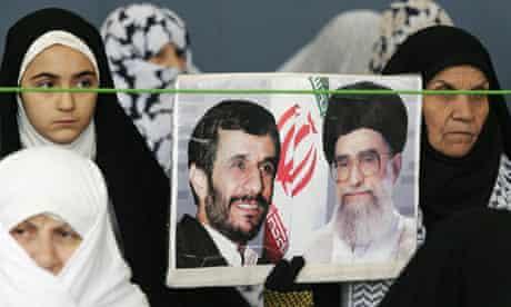 Iranian women hold portraits of Mahmoud Ahmadinejad and Ayatollah Ali Khamenei at Friday prayers