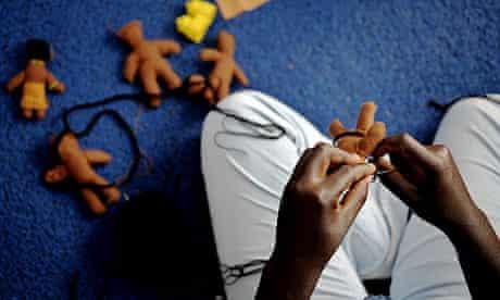A Kenyan woman creates puppets at one of Nairobi's slums