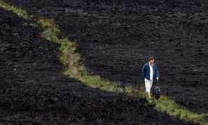 A man walks with his dog in Dorset Heath after a fire in Dorset