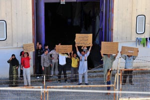 Syrian refugees: Syrian refugees hold up placards at the Turkish Red Crescent camp