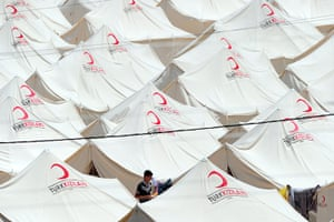 Syrian refugees: A Syrian refugee walks past tents at the Boynuyogun Red Crescent camp