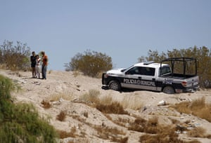 FTA: Tomas Bravo: People stand next to a patrol car at a crime scene