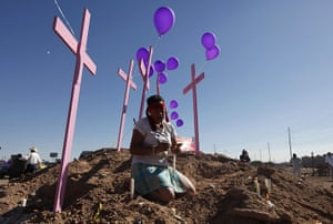 FTA: Tomas Bravo: A woman prays next to pink crosses erected in memory of women murdered