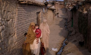 Women with a baby walk in a slum alley on the outskirts of Islamabad, Pakistan